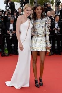 Las modelos Doutzen Kroes con un vestido blanco de corte asimétrico de Atelier Versace Spring 2015 y Liya Kebede con un corto vestido de manga larga de Louis Vuitton.