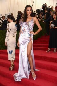 Irina Shayk con un vestido lila asimétrico con estampados de la firma Atelier Versace.