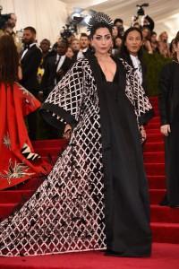 Lady Gaga, muy acertada, con un vestido negro de corte princesa y un original abrigo de la firma Balenciaga.