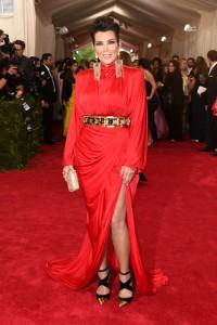 Kris Jenner con un vestido rojo de manga larga y gran corte lateral en la falda de la firma Balmain.