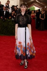Lilly Collins con un dos piezas compuesto por blusa negra con transparencias y falda blanco con estampado floral de la firma Chanel colección Haute Couture Spring 2015.