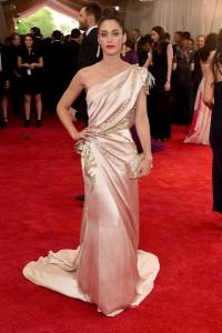Lizzy Caplan con un vestido rosa pálido con estampados dorados de Donna Karan Atelier.
