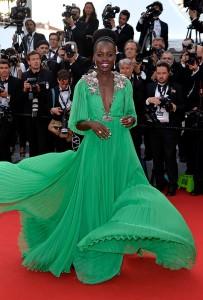 Lupita N'yongo con un vestido plisado verde con un gran escote de la firma Gucci.