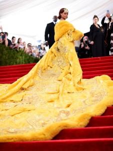 Rihanna con un vestido amarillo acompañado de un abrigo con una gran cola del mismo color con bordados del diseñador Guo Pei Couture.