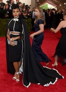 Janelle Monaé, muy elegante, con un original traje de tres piezas: top, falda y capa en negro con ribete blanco de la firma H&M.