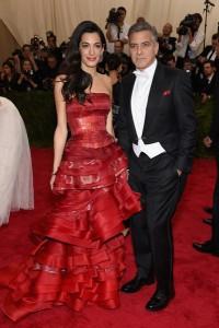 Amal Clooney con su marido George Clooney con un elegante vestido rojo de Maison Margiela diseñado por John Galliano.