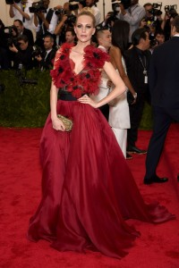 Poppy Delevigne con un vestido rojo de corte princesa con flores rojas en la parte superior de la firma Marchesa.