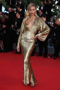 Natasha Poly con un vestido dorado de manga larga ancha y gran escote del diseñador Michael Kors.