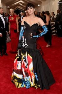 Katy Perry con un vestido de corte sirena negro con estampados diseñado por Jeremy Scott para Moschino colección fall 2015.