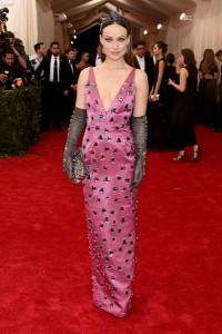Olivia Wilde con un vestido rosa con incrustaciones y guantes grises de la firma Prada.