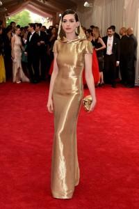 Anne Hathaway con un vestido dorado con capucha de Ralph Lauren Collection.