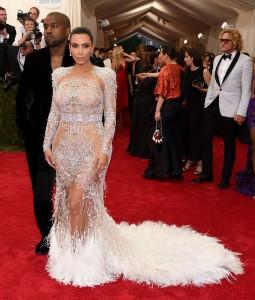 Kim Kardashian, acompañada de Kanye West, con un vestido blanco con transparencias y cola de plumas de Roberto Cavalli.