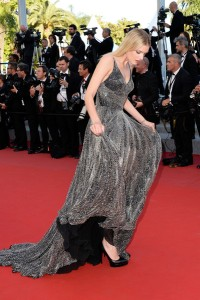 Lily Donaldson con un vestido plateado sobre un fondo negro de la firma Saint Laurent.