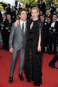Sienna Miller, miembro del jurado, acompañada de Xavier Dolan, con un vestido negro de gasa con estampado de estrellas de la diseñadora Sonia Rykiel colección Pre-Fall 2015.