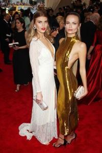 Maryna Linchuk con un vestido blanco escotado de manga larga y Natasha Poly con un vestido dorado, los dos de la firma TopShop.