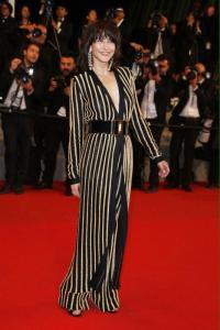 Sophie Marceau con un vestido de rayas negras y doradas de la firma Balmain.
