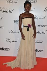 Lupita N'yongo con un vestido color crema de la firma Gucci.