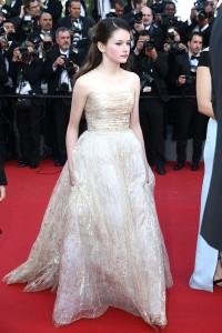 Mackenzie Foy con un vestido de corte princesa de blanco con estampados dorados de Oscar de la Renta colección Pre-Fall 2015.