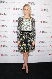 Taylor Schilling con un vestido de manga larga de fondo oscuro.
