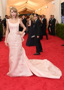 Taylor Swift con un vestido rosa con estampado dorado y cola.