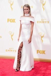 Renée Bargh con un vestido blanco de Daniel Avakian acompañadas de unas sandalias por encima de la rodilla.