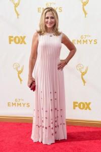 Eddie Falco con un vestido rosa pálido con pequeño estampado rojo de la firma Prada.