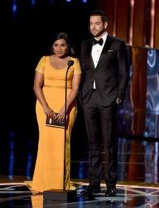 Mindy Kaling, entregando un premio con Zachary Levi, con un vestido amarillo mostaza del diseñador Salvador Perez.